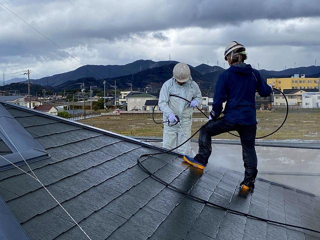 屋根の洗浄をする作業員