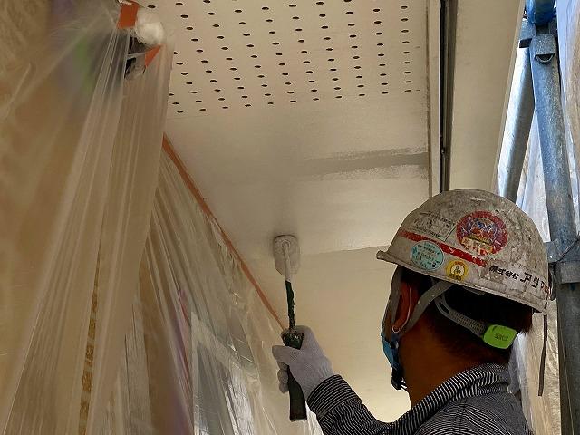 軒天をローラーで塗る作業員