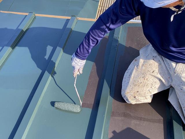屋根を塗装する作業員