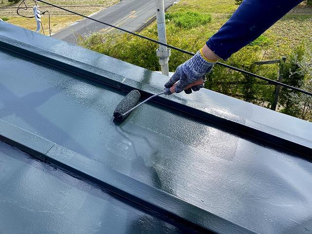 屋根の上塗りをする作業員