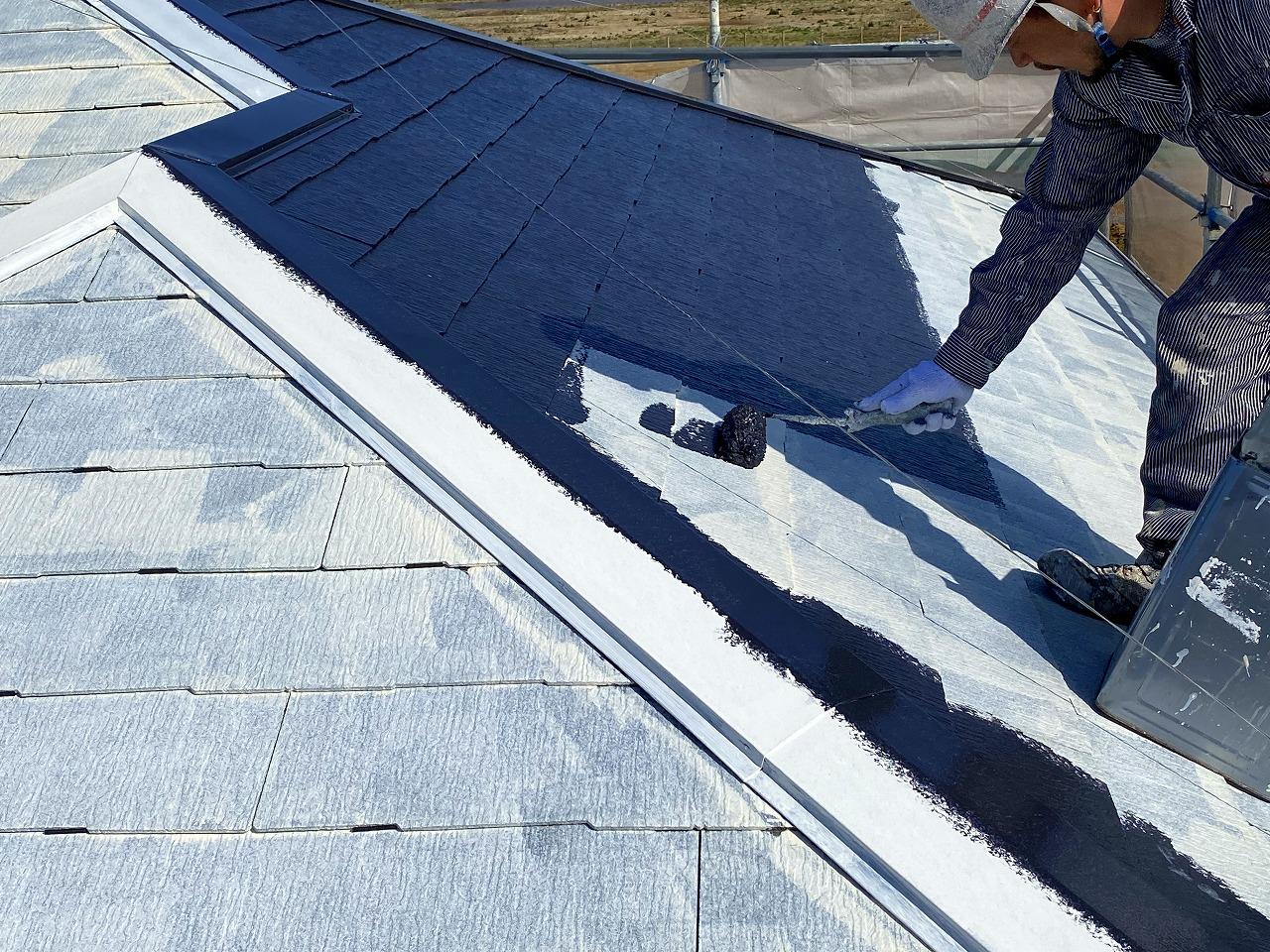 屋根の中塗りをしている作業員
